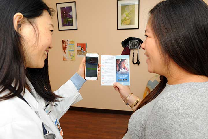 Dr. Cheryl Twu explaining how to use the Hapai app to patient Marissa Emoto-Tasda