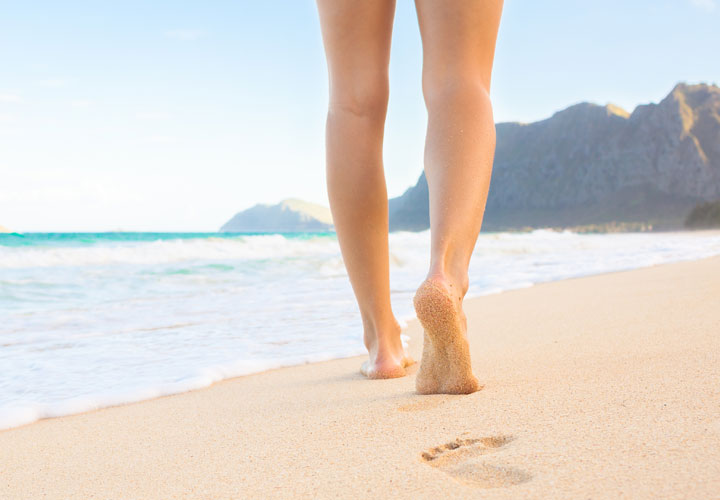 Veins Clinic woman walking on beach